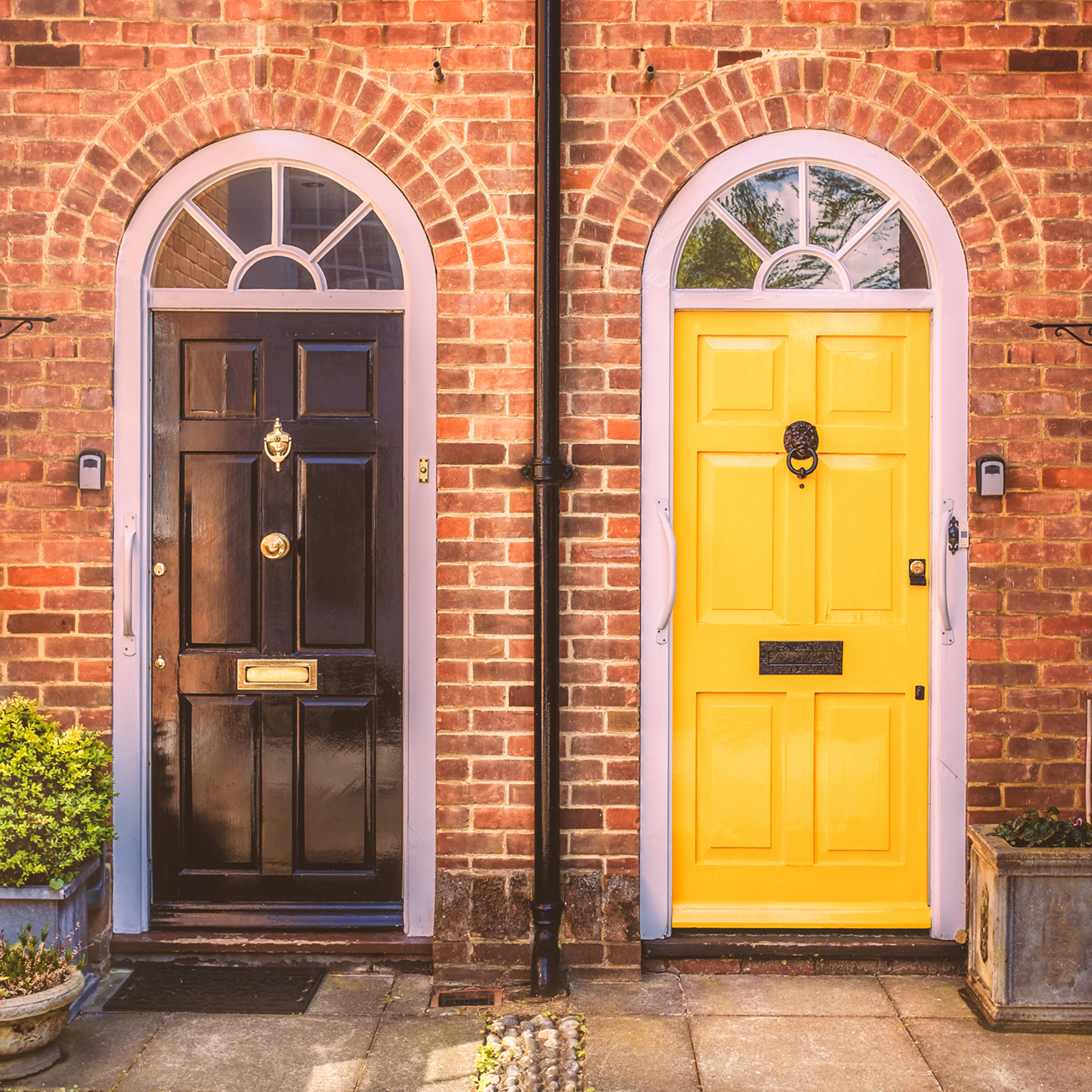 Two residential front doors, one black one yellow and a red bric